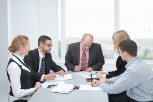 businesspeople formed of men and women in an office at a table